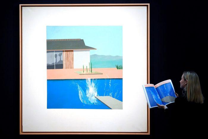 O quadro 'The Splash', de David Hockney, é admirado por funcionária antes do leilão na Sotheby's de London — Foto: Toby Melville/Reuters