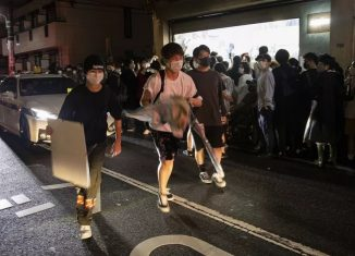 Homens carregam obras de arte após entrarem em galeria de arte de Tóquio que sugeria que visitantes 'roubassem' as obras que quisessem — Foto: Behrouz MEHRI / AFP