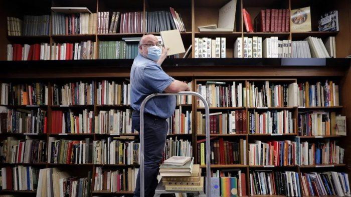 Homem usando máscara de proteção organiza livros na livraria La Sorbonne, na França — Foto: Eric Gaillard/Reuters