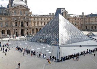 Visitantes fazem fila para entrar na pirâmide do Louvre, em Paris, nesta segunda-feira (6), quando o museu reabre suas portas ao público após quase quatro meses de fechamento por causa da Pandemia de Covid-19 — Foto: Charles Platiau/ Reuters